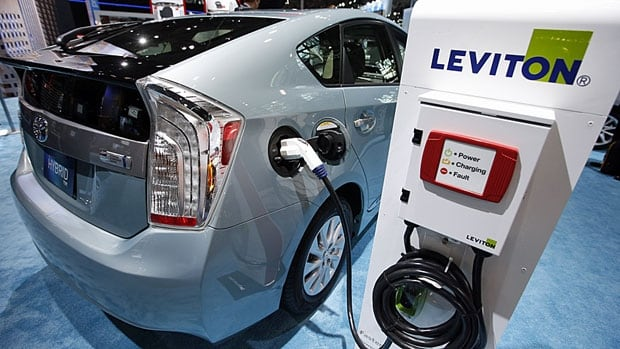 A 2013 Toyota Prius plug-in hybrid car is plugged into a Leviton charging station at the New York auto show. Because of new fuel standards, auto companies are suddenly at the forefront of innovation and R&D, according to a recent report.