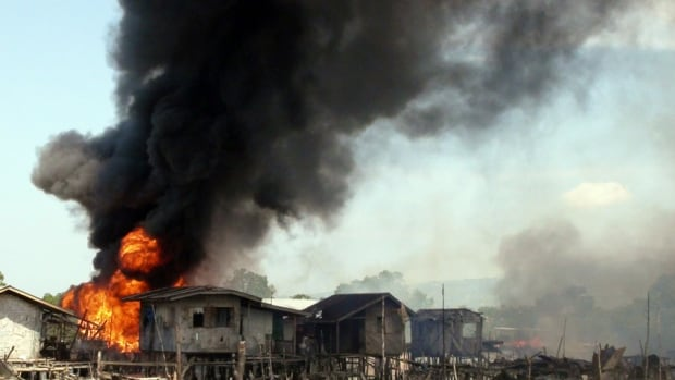 Smoke billows as stilt houses burn in fires caused by fighting between government soldiers and Muslim rebels of the Moro National Liberation Front in the outskirts of Zamboanga city, southern Philippines on Friday.