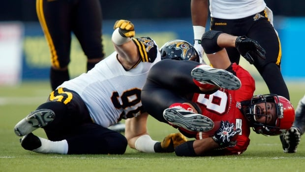 Hamilton Tiger-Cats' Brian Bulcke, left, brings down Calgary Stampeders' Jon Cornish, during first quarter CFL football action in Calgary, Alta., on Sept. 13, 2013.
