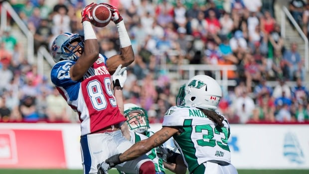 Montreal Alouettes' Duron Carter, left, makes a catch as Saskatchewan Roughriders' Craig Butler, centre, and Dwight Anderson during the first half Sunday.