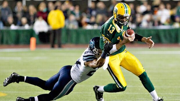 Toronto Argonauts' Shane Horton, left, tackles Edmonton Eskimos' Mike Reilly in Edmonton, Alta., on Saturday September 28, 2013.
