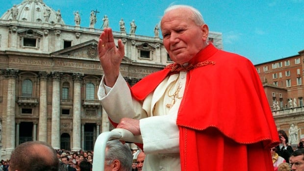 In this file photo from 1997, Pope John Paul II waves to the faithful as he crosses St. Peter's Square at the Vatican. Popes John Paul II and John XXIII will be declared saints on April 27, 2014, Pope Francis announced Monday.