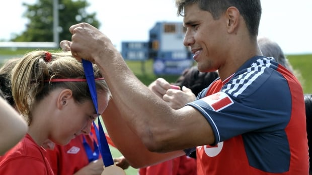 Toronto FC's Adrian Cann congratulates gold medal winners, the Brampton Brams United Bandits, at the Ontario Summer Games soccer match in Toronto, Sunday, August 19, 2012.  MARKETWIRE PHOTO/BMO Financial Group/BMO Bank of Montreal