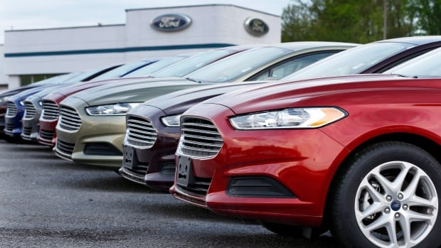 A row of new 2013 Ford Fusions is seen at an automobile dealership. Ford's car and light truck sales continued to rise in September and sales of the Fusion were up 20 per cent.