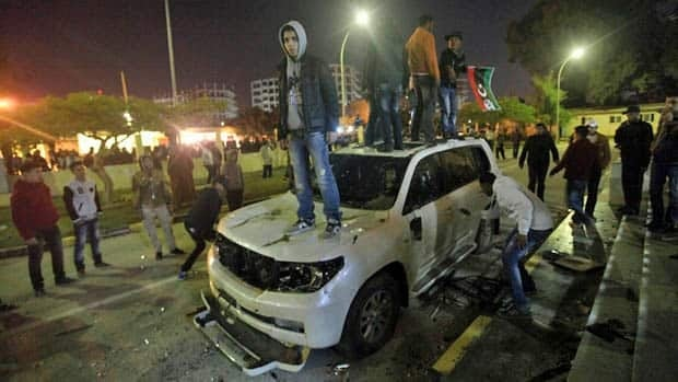 Protesters damage a car outside the National Transitional Council headquarters of Benghazi.