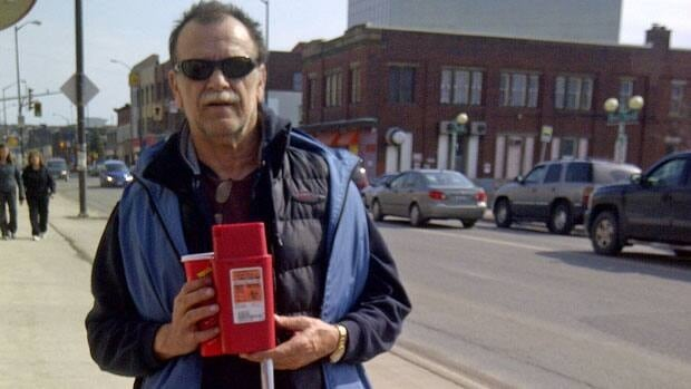 Len Frappier, the co-ordinator of The Point, carries tongs and a plastic biohazard container, as he walks around Sudbury's downtown, picking up needles.