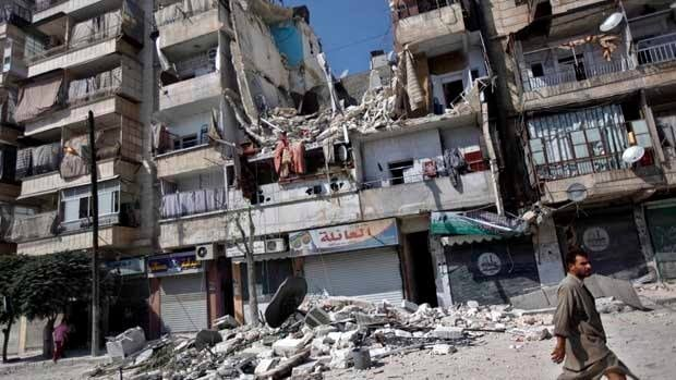 A man walks by a building destroyed in an airstrike in Aleppo on Friday. Rebel footholds in the city have been the target of weeks of Syrian shelling and air attacks as part of wider offensives by President Bashar Assad's regime.