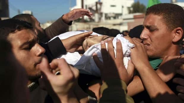 Palestinians carry the body of Hamas militant Mohammed Qanoua, who died of wounds suffered from Israeli tank fire, during his funeral in Gaza City on Nov. 13, 2012.