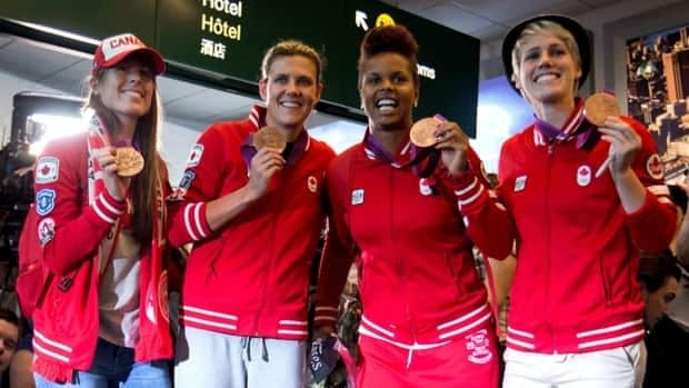 Canadian women's soccer team players Emily Zurrer, from left, captain Christine Sinclair, Karina LeBlanc and Sophie Schmidt show off their bronze medals from the London Olympics at Vancouver International Airport in Richmond, B.C., on Monday, August 13, 2012.