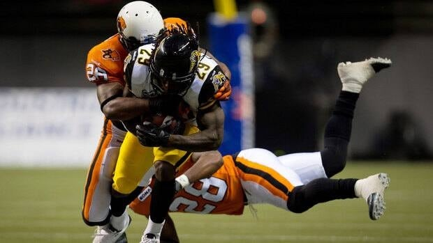 Hamilton Tiger-Cats' Chevon Walker, centre, is brought down by B.C. Lions' Anthony Reddick, left, and Byron Parker during the second half Friday.