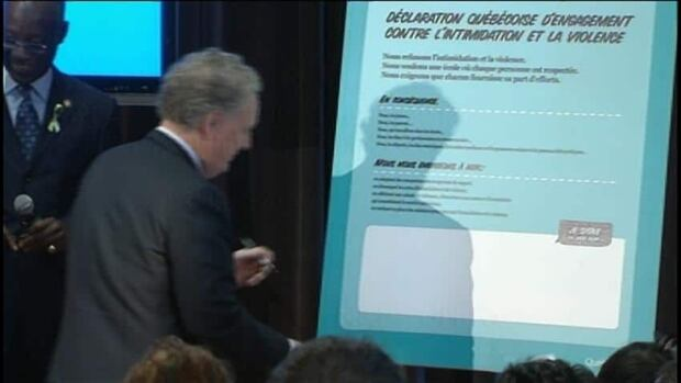 Quebec premier Jean Charest signs an anti-bullying declaration, one of a handful of new measures introduced to counter intimidation among youth.