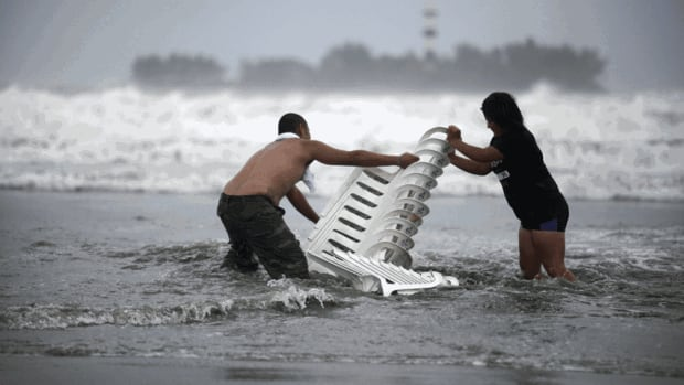 Vendors that were caught unprepared in Tropical Storm Ernesto try to recover their chairs after high waves dragged their beach stalls into the sea in Veracruz, Mexico, on Thursday.