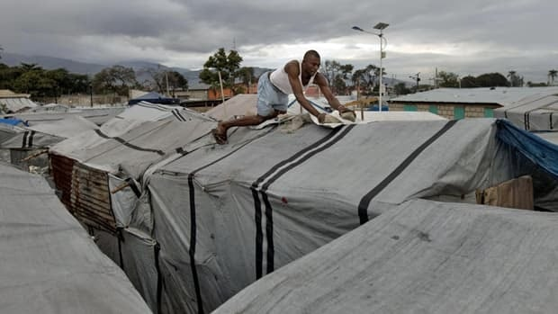 Pirist Dugard, 31, places rock on a tarp covering his tent at a camp set up for people displaced by the 2010 earthquake, in what used to be an airstrip in Port-au-Prince, Haiti, on Jan. 4, 2012. More than 500,000 Haitians remain in camps two years after the quake.