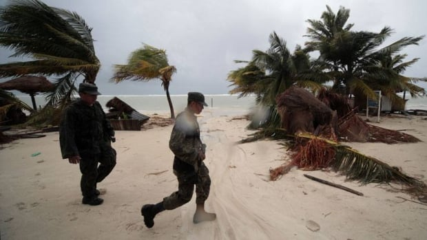 Soldiers walk past palm trees knocked down by Ernesto in Mahahual, in the Mexican state of Quintana Roo.