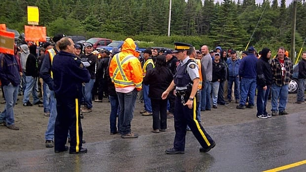 Police are on the scene where more than 100 crane operators are standing at the turnoff from the Trans-Canada Highway to the Long Harbour access road.