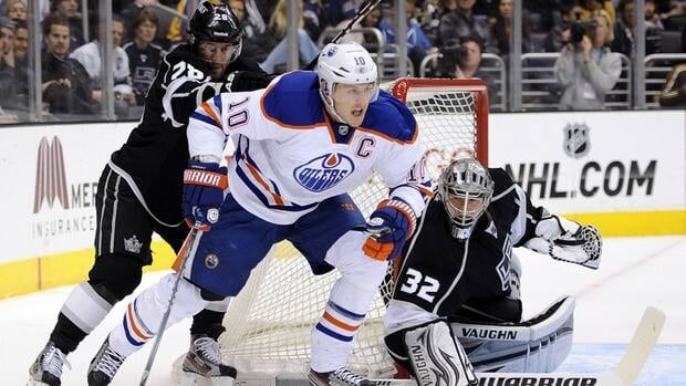 Edmonton Oilers forward Shawn Horcoff, centre, comes around the net in front of Jarret Stoll and Jonathan Quick, right, of the Los Angeles Kings during the first period on Monday.