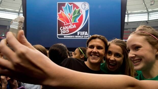 Team Canada's Christine Sinclair takes a photo with young soccer fans as FIFA unveils the official emblem for the 2015 Women's World Cup in downtown Vancouver, B.C. on Friday.