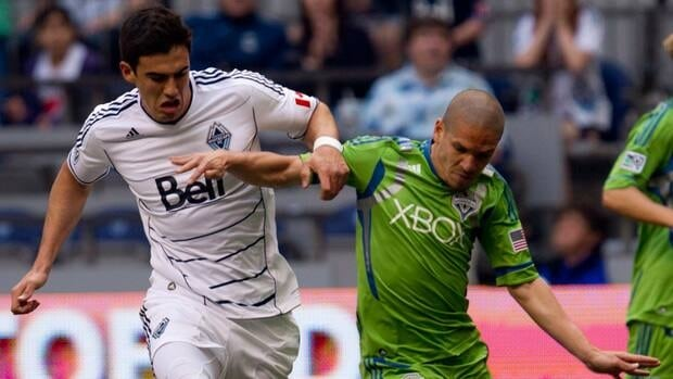 Vancouver Whitecaps' Omar Salgado fights for control of the ball with Seattle Sounders Osvaldo Alonso in their previous match on May 19.