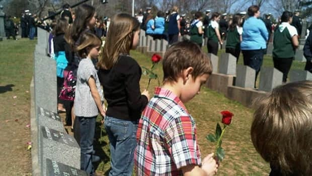 Children stand behind gravestones for each of the Titanic victims buried in Fairview Lawn Cemetery, Halifax.