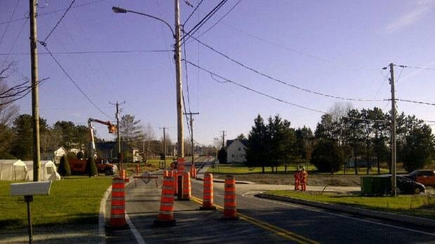 A construction crew paved around a utility pole inside a lane near Johnville in Quebec's Eastern Townships, pictured here earlier this week.