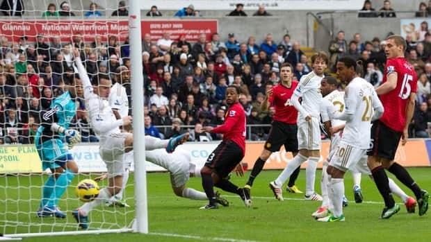 Manchester United's Patrice Evra, centre, scores against Swansea on Sunday.
