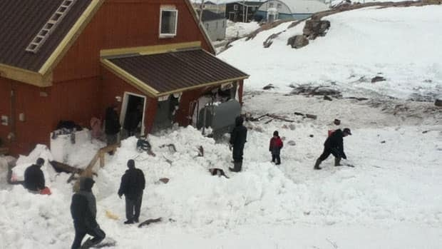 Members of the community help to clear snow, slush and water after a flash flood damaged a home in Kimmirut, Nunavut, on Sunday.