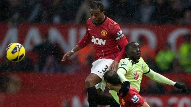 Manchester United's Patrice Evra, top, and Ryan Giggs fight for the ball against Newcastle United's Papiss Demba Cisse on Wednesday. United won to retain it's strong hold on the Premiership.