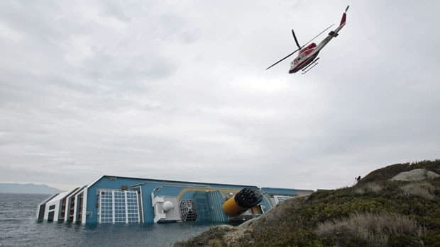 A firefighters' helicopter flies over the Costa Concordia  on Monday, two days after the luxury cruise liner ran aground off the tiny Tuscan island of Giglio, Italy.