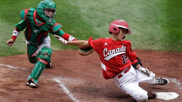 Vancouver's Thomas Neal, right, scores past Nuevo Laredo, Mexico's Marcelo Perez on a two-run double by Cortez D'Alessandro in the first inning at the Little League World Series on Friday.