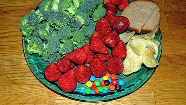 A plate showing portion sizes of 100 calories worth of strawberries, broccoli, potato chips, bread and M&Ms used to counter the perception that it's cheaper to eat junk food than a nutritionally balanced meal.