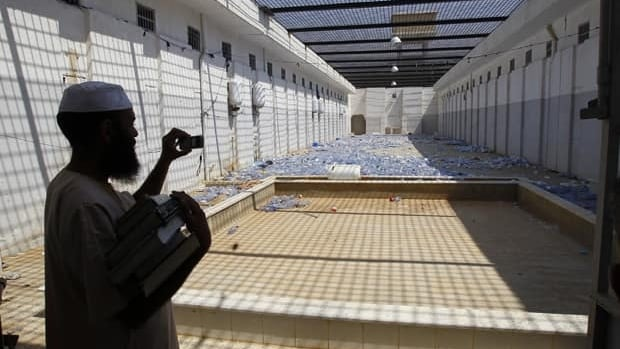 In this August 2011 file photo, a Libyan man takes pictures of the courtyard of Abu Salim prison, in Tripoli. Human Rights Watch says it has uncovered evidence of a wider use of waterboarding in U.S. interrogations of detainees than has been acknowledged.