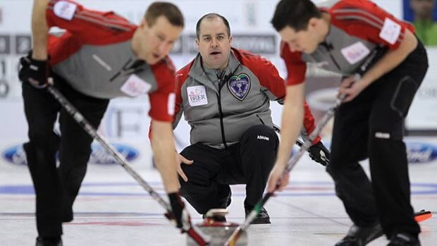 NWT/Yukon skip Jamie Koe, centre, watches his shot as second Brad Chorostkowski, left, and lead Robert Borden sweep during a morning draw against New Brunswick at the Tim Hortons Brier in Saskatoon, Sask., on Thursday.