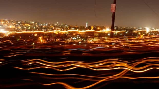 Streams of light trail people walking with candles during Earth Hour in Amman, Jordan, in this long-exposure photograph.