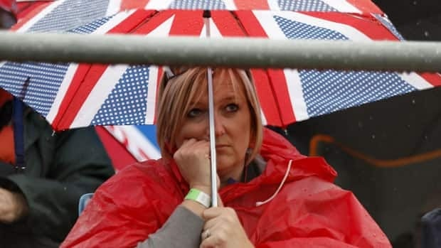A Formula One racing fan waits for marshals to allow a resumption of qualifying for the British F1 Grand Prix at Silverstone, central England, Saturday.