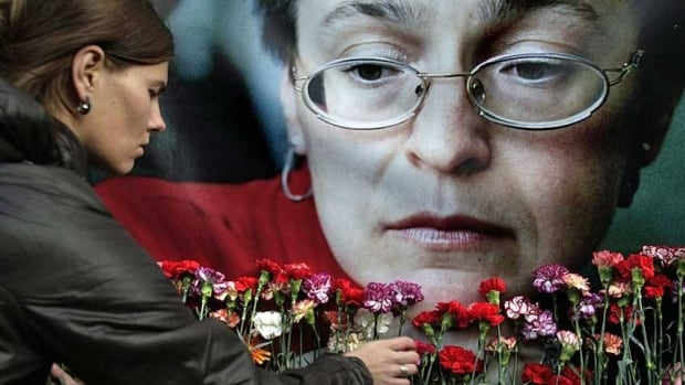 A woman places flowers before a portrait of slain Russian journalist Anna Politkovskaya in Moscow in 2009.  A former Moscow policeman has been convicted of helping in the murder.
