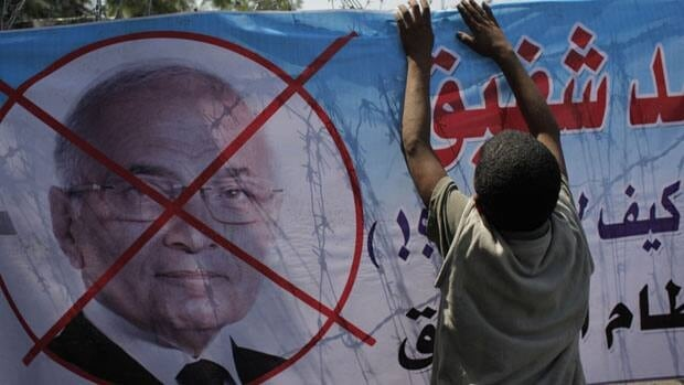 An Egyptian youth hangs a banner with a defaced picture of presidential candidate, Ahmed Shafiq. Egypt's highest court ruled Thursday that Shafiq can stay in the presidential race.