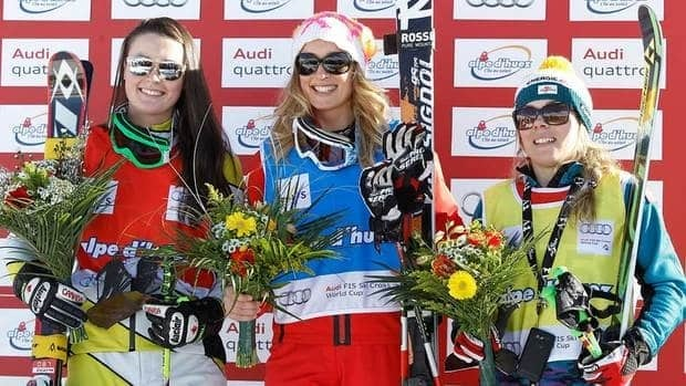 Sanna Luedi, of Switzerland, center, winner of the women's ski cross World Cup event of the Alpe d'Huez, French Alps, celebrates on the podium with Marielle Thompson of Canada, left, who finished second, and Andrea Limbacher of Austria, right, who came third.
