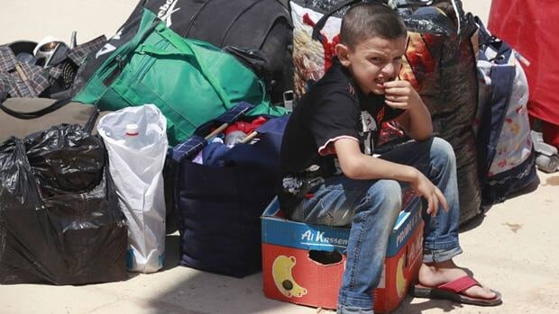 A Syrian refugee boy sits beside bags as he arrived at the border crossing by the Iraqi town of Qaim, 320 kilometres west of Baghdad, Iraq.