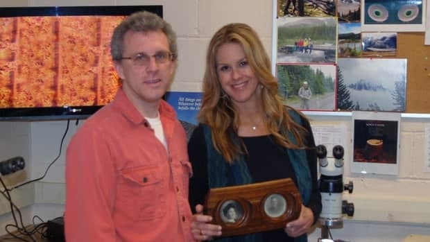Elyse Luray, right, of PBS's History Detectives program, holds a picture frame that some allege is made of wood from a stair rail on the Titanic. Standing next to her is Colin Laroque, head of Mount Allison University's dendrochronology lab, who was asked to verify the wood's provenance.