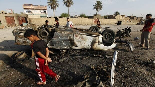 Residents gather at the site of a car bomb attack in Mahmudiya, south of Baghdad. A wave of attacks across Iraq on Monday left dozens dead.