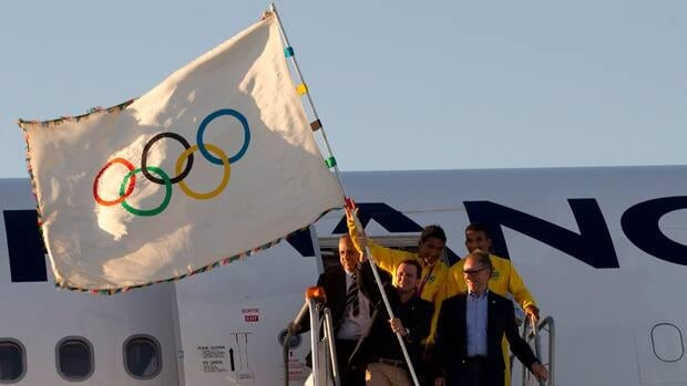 Rio de Janeiro's Mayor Eduardo Paes, top left, Carlos Arthur Nuzman, President of the Brazilian Olympic Committee, bottom right, and Brazilian athletes hold up the Olympic flag upon its arrival in Rio de Janeiro on Aug. 13.