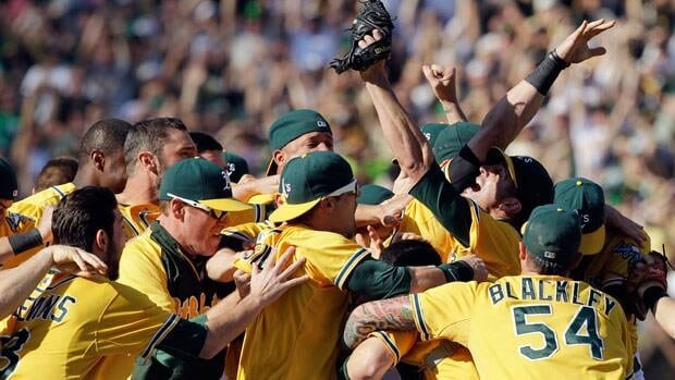Oakland Athletics relief pitcher Grant Balfour, third right looking, up celebrates with teammates after their 12-5 win over the Texas Rangers on Wednesday.