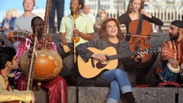 Singer Rosanne Cash is surrounded by diverse musicians in this scene from the Land of Dreams television ad that was filmed at the Brooklyn Bridge in New York.