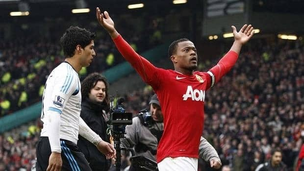 Patrice Evra, right, celebrates in front of Liverpool's Luis Suarez after a Saturday game that began with Suarez refusing to shake Evra's hand. Suarez had just come off an 8-game suspension for making racist remarks to Evra.