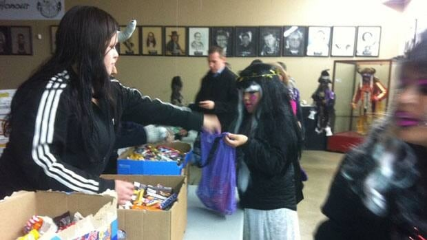 A volunteer hands out candy to children at the Indian and Metis Friendship Centre's safe Halloween event late Wednesday afternoon.