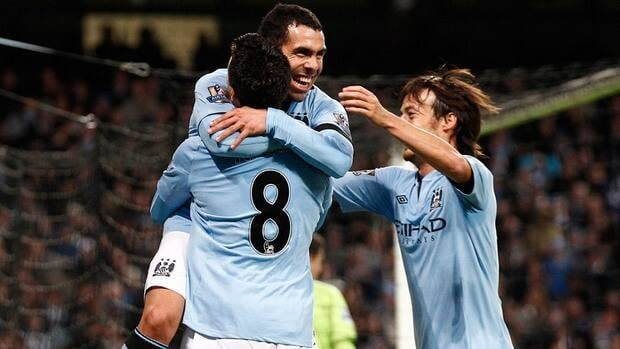 Manchester City's Carlos Tevez, top, celebrates with teammates Samir Nasri and David Silva, right, after scoring his second goal against Aston Villa during their match on Saturday.