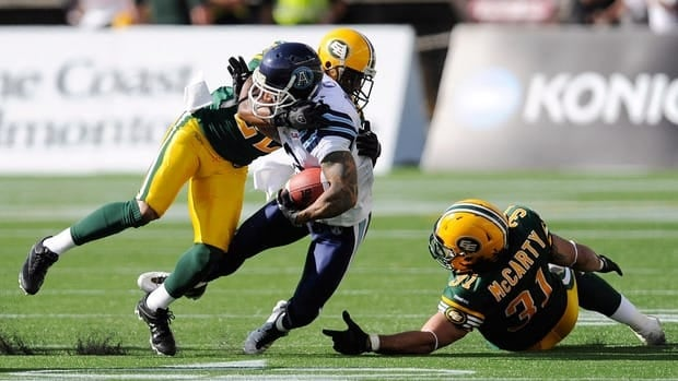 Edmonton Eskimos Joe Burnett, rear, tackles the Toronto Argonauts Chad Owens as Eskimo Calvin McCarty falls, right, during the first half in Edmonton on Saturday.