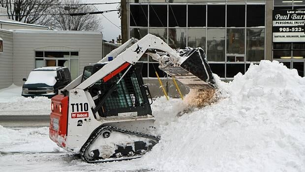 A digger clears snow from a sidewalk in downtown Hamilton. The city received 13 cm of snow during its first major winter storm of the season.