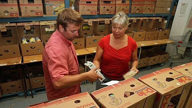 Volunteer Marc Robert and food bank program manager Lisa Burrows sort food at the Salvation Army food bank on Bay Street. (Samantha Craggs/CBC)