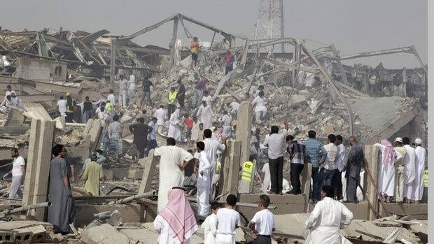 People walk among rubble at the site of a fuel truck explosion in Riyadh, Saudi Arabia.